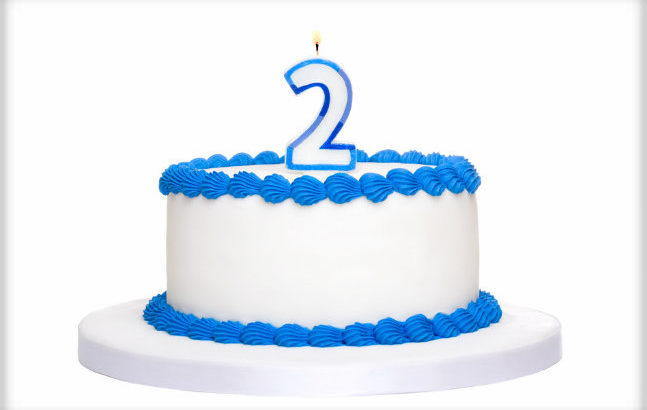 Birthday cake decorated with blue frosting and number two candle